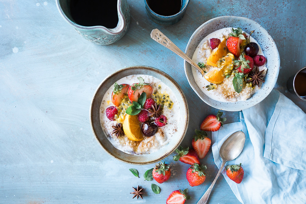 two bowls of oatmeal topped with fruit