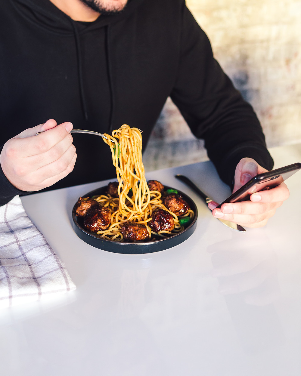 person eating spaghetti while looking at their phone