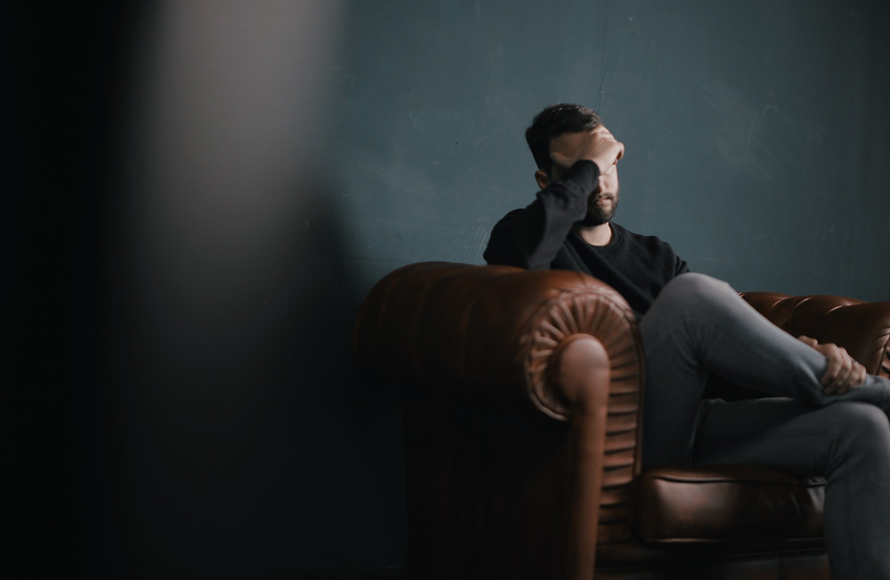 man sitting on a couch with his head in his hand