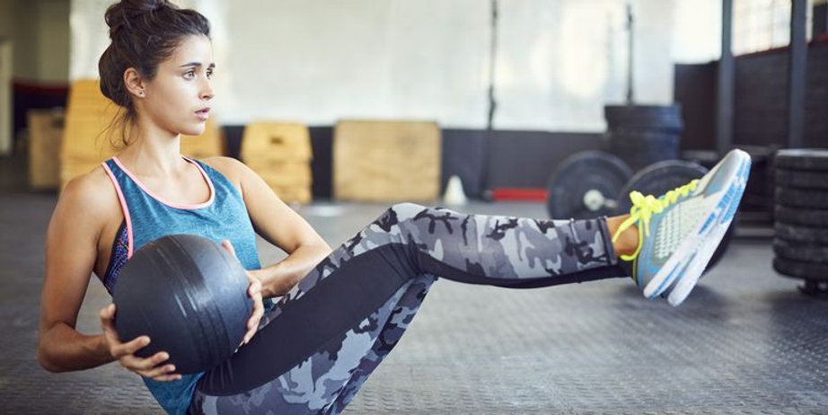 determined-woman-exercising-with-medicin