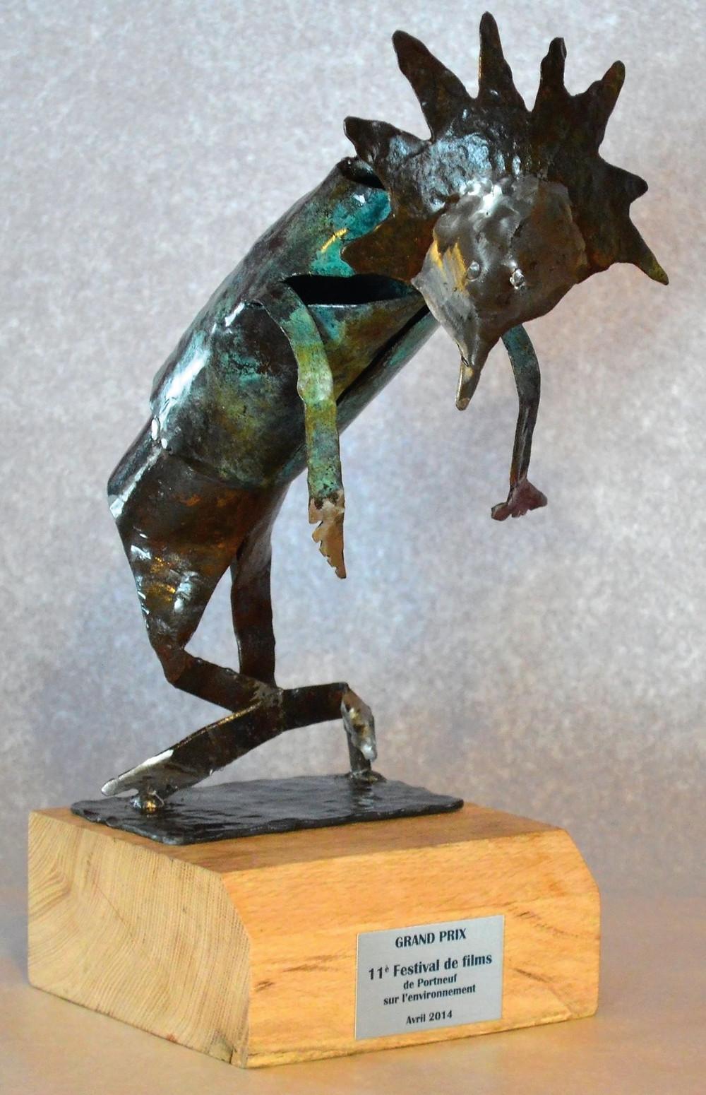 La statuette du 11è  FFPE a été fabriqué à partir de l'idée originale de Valentina Florez-Lopez,. Fabriquée d'acier chauffé sur feu de forge, martelée pour en découvrir ses formes, assemblée par soudures et rivets, colorée par oxydation et polis. Un verni est appliqué pour en conserver ses couleurs. La base est fabriquée à partir d'un vieux madrier de chêne recyclé et d'huile de lin. Le nom du gagnant est gravé le jour du vote final par pyrogravure. La statuette est signée Ferboi.
