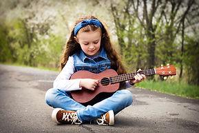 Pretty young girl playing ukulele in the