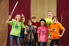 Young actors holding costume pieces smil