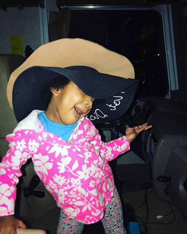 Toddler with moms hat on posing