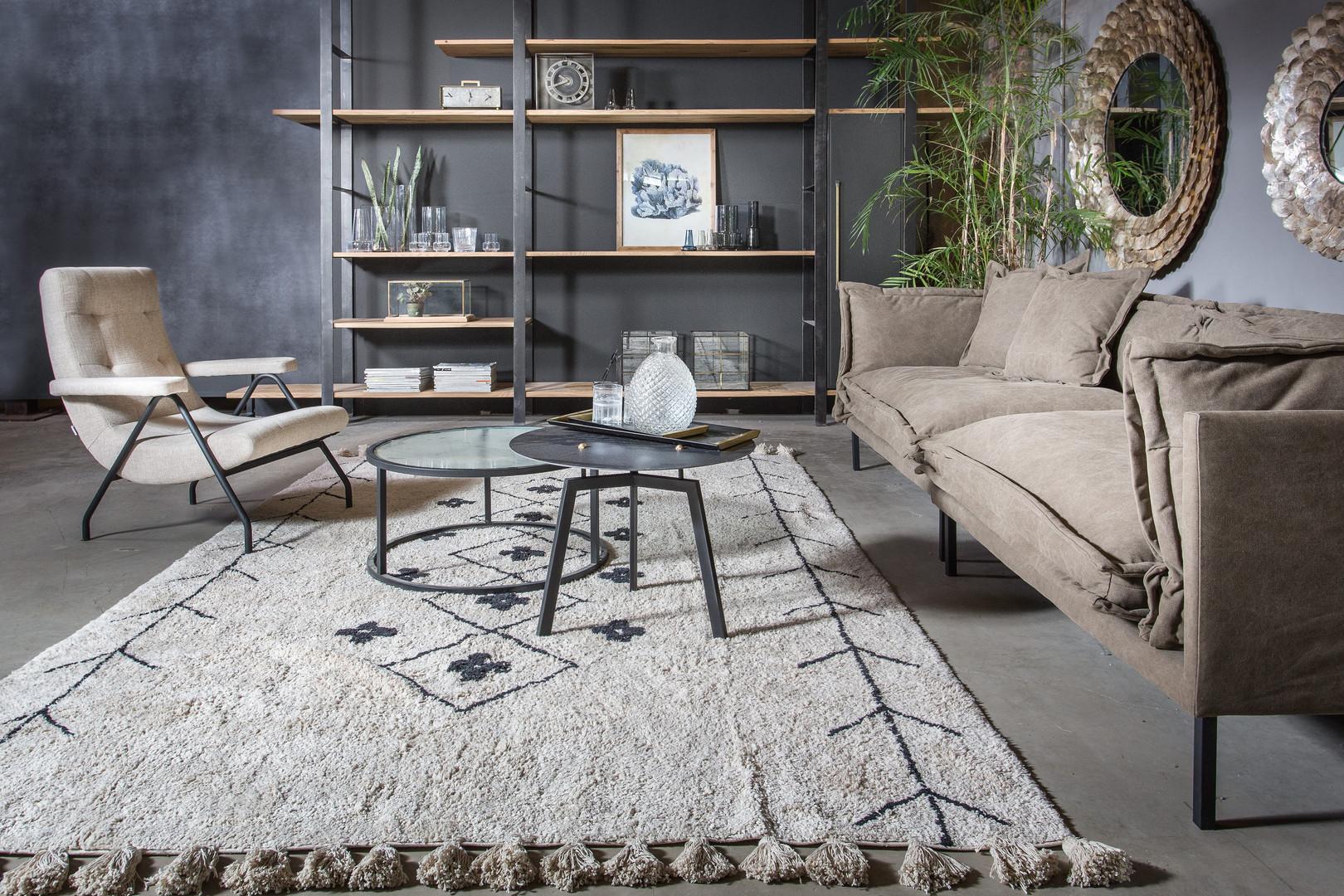 ספה בסגנון סקנדינבי על רקע קיר תעשייתי בשילוב שטיח ברברי