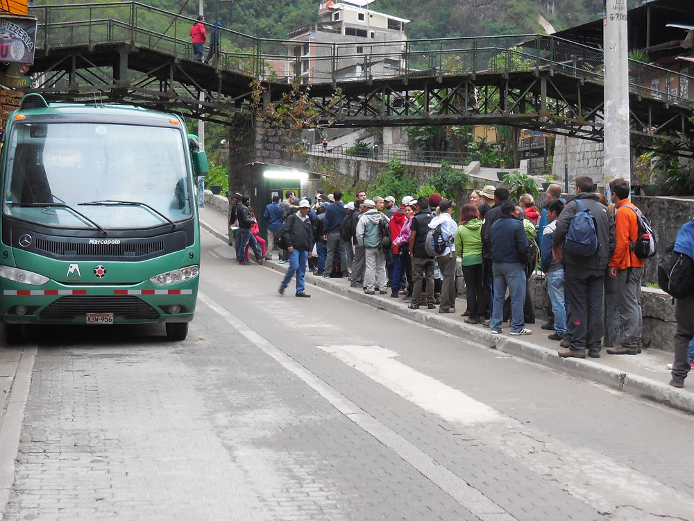 A bus prepares to leave Aguas Calientes for the 25-minute trip to Machu Picchu while people wait to purchase their bus ticket
