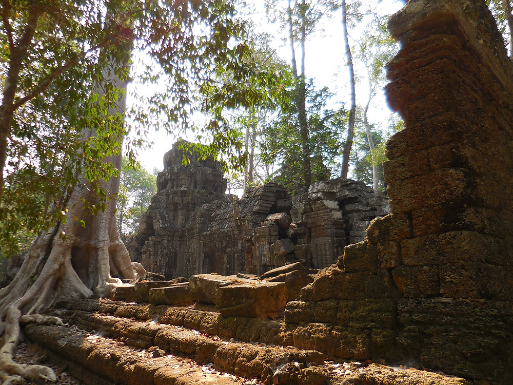 Looking over a partially collapsed wall to the crumbling temple walls of Ta Nei