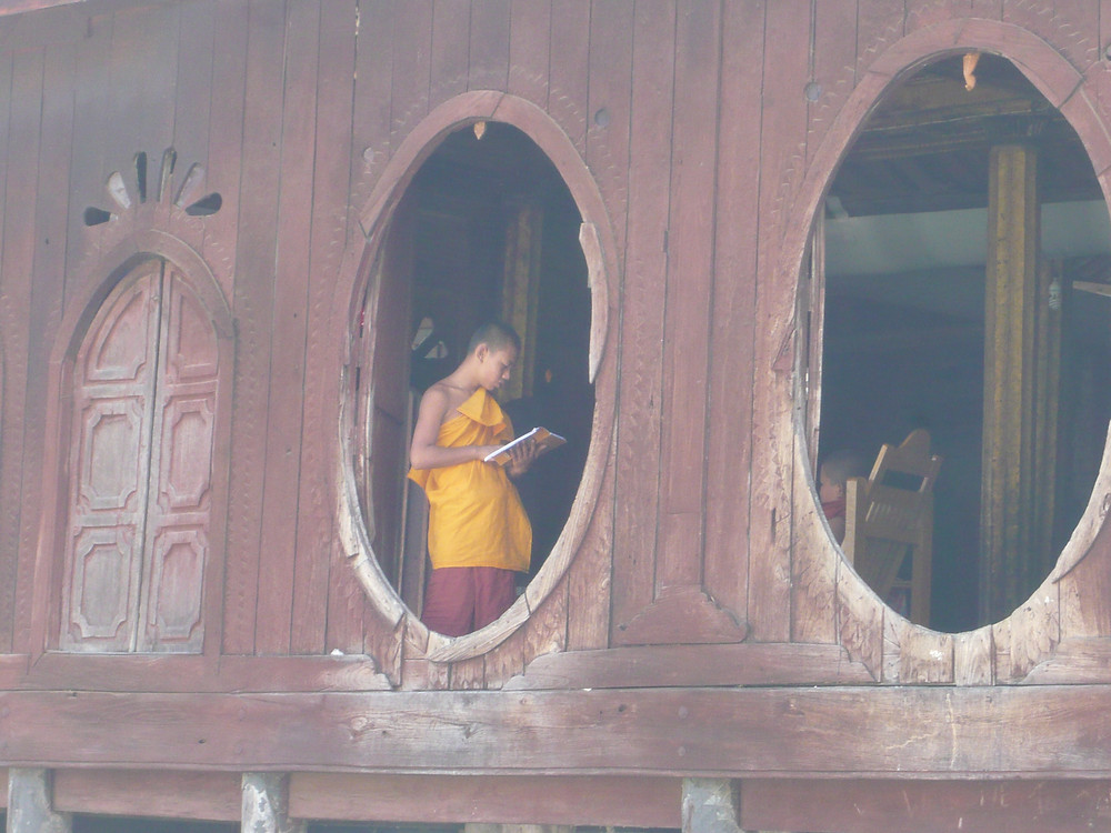 A monk reading while standing in the window at Shwe Yan Pyay Monastery