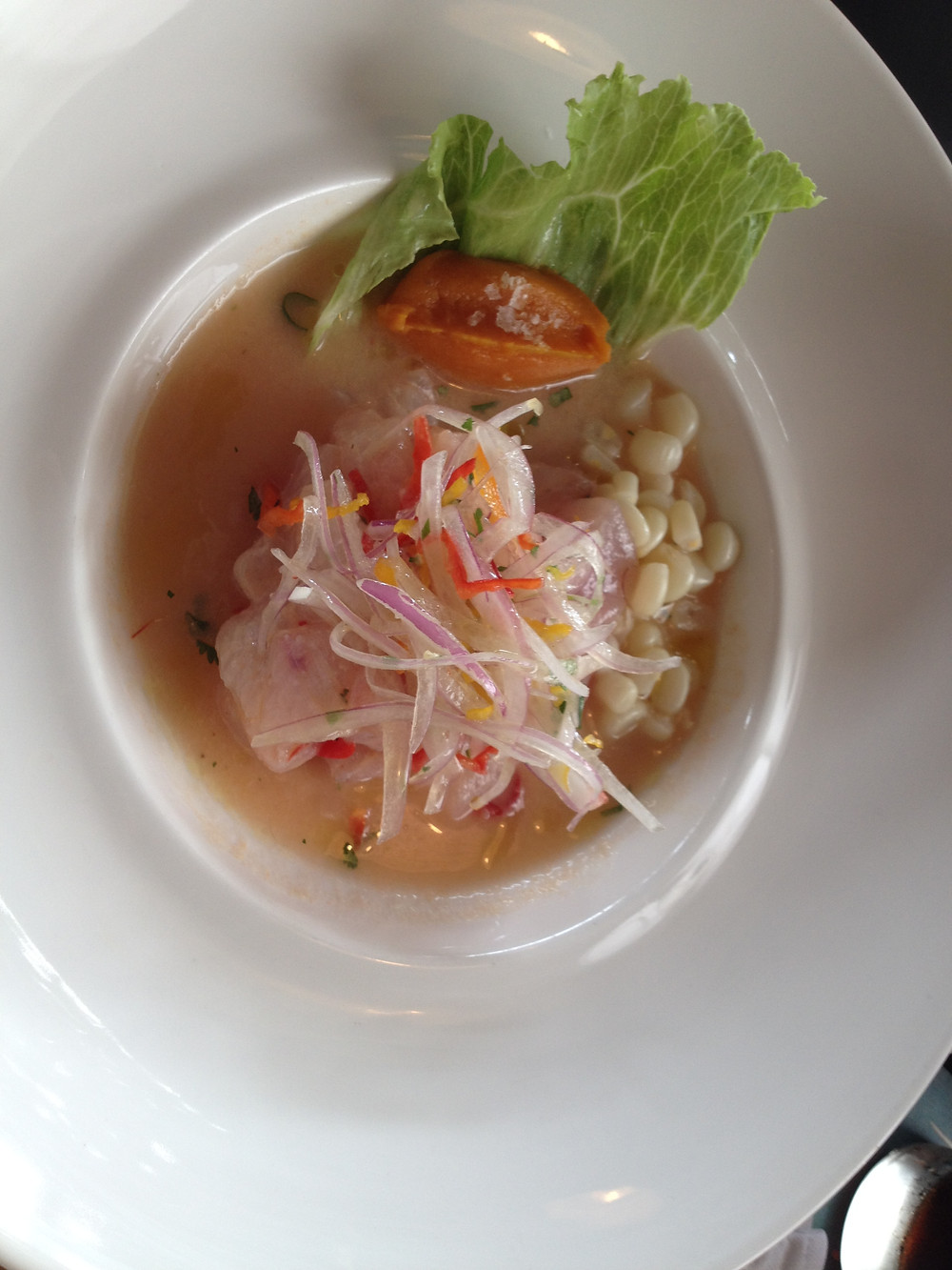 """Ceviche de lenguado (sole) at El Mercado – simply cooked in lime juice and red chili """"tiger milk"""" with red onion, cilantro served with iceberg lettuce, sweet potato and corn"""