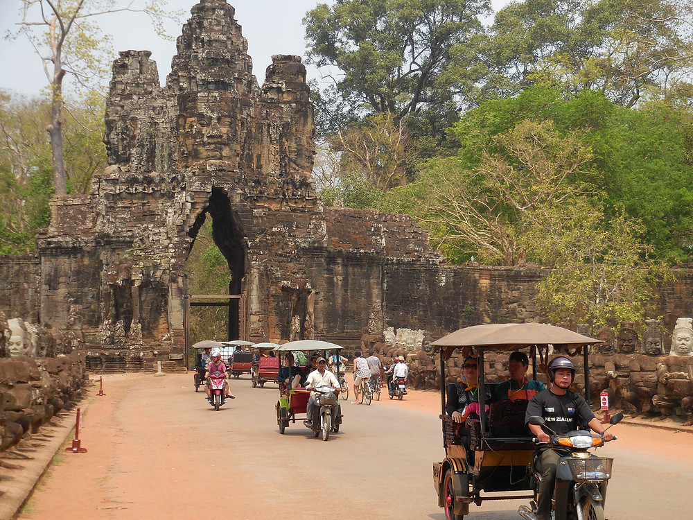 Tuk tuks crowd the causeway in front of the South Gate of Angkor Thom