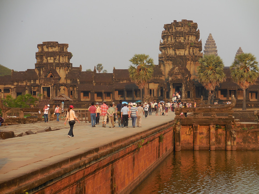 Crossing the moat and approaching the outer walls of Angkor Wat. The late day sun brings out its colors.