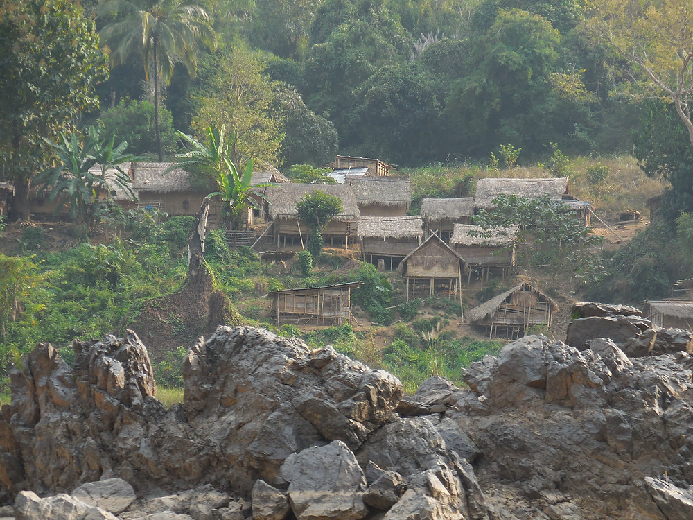 A village, along the Mekong River, is situated on the steep hillside