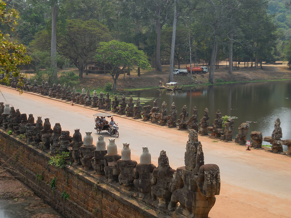 A solo tuk tuk crosses the causeway heading to the south gate of Angkor Thom