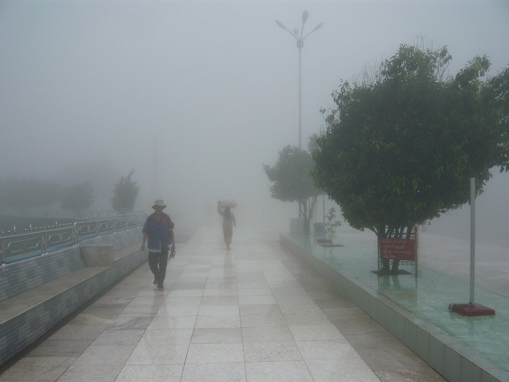 Locals walking in the fog, wind and rain at the top of My Kyaiktiyo near the Golden Rock