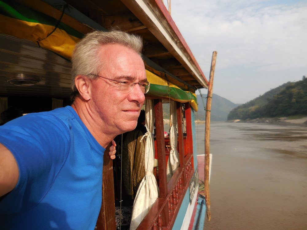 John gazing at the scenery as he heads down the Mekong River