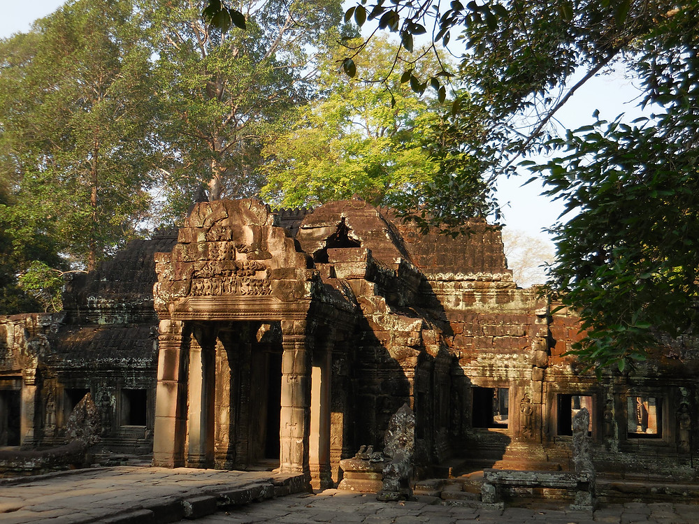 The morning sun filters through the trees hitting the east-facing entrance to Banteay Kdei