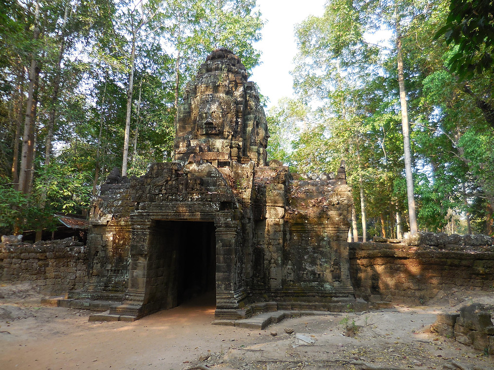 The gopura, or outer wall entrance, to Ta Som. Notice the stone faces, on top, each facing a cardinal point.