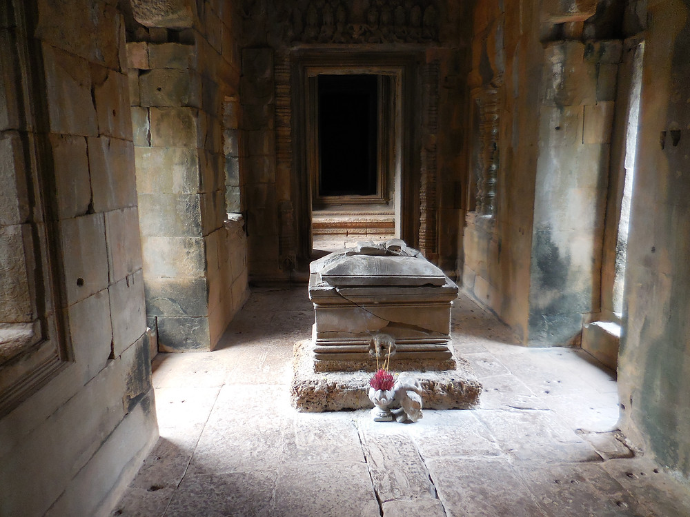 Inside one of the buildings, the morning sun shines on a coffin-like object