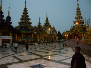 A monk strolling, in the rain, at the Shwedagon Pagoda