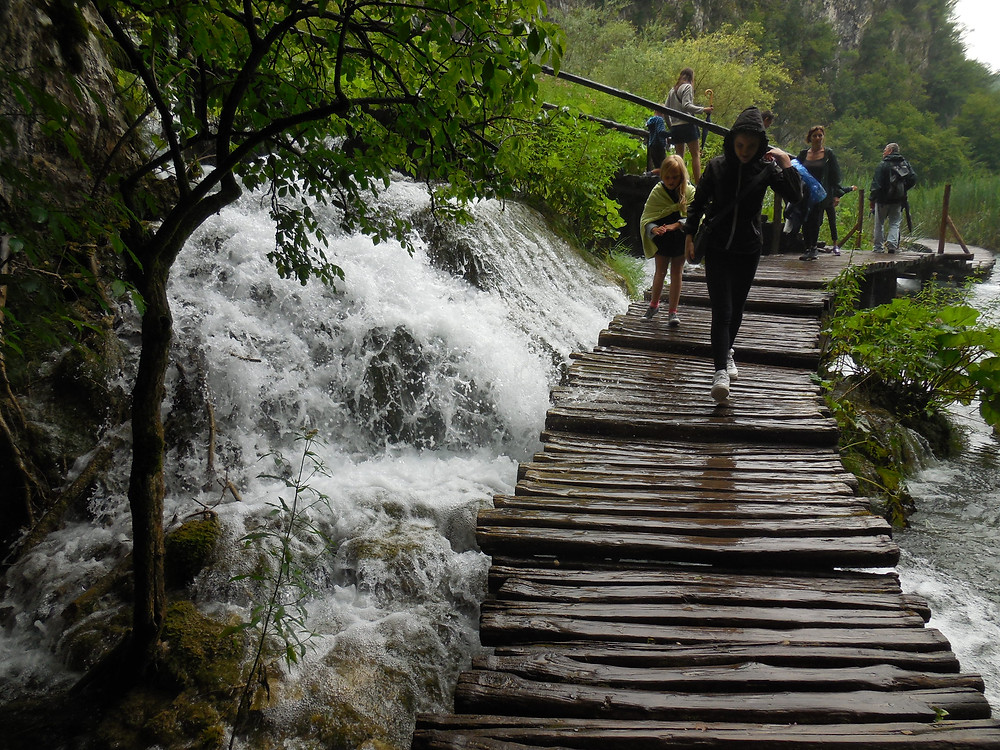 A woman tries to avoid the water that's cresting the top of the walkway