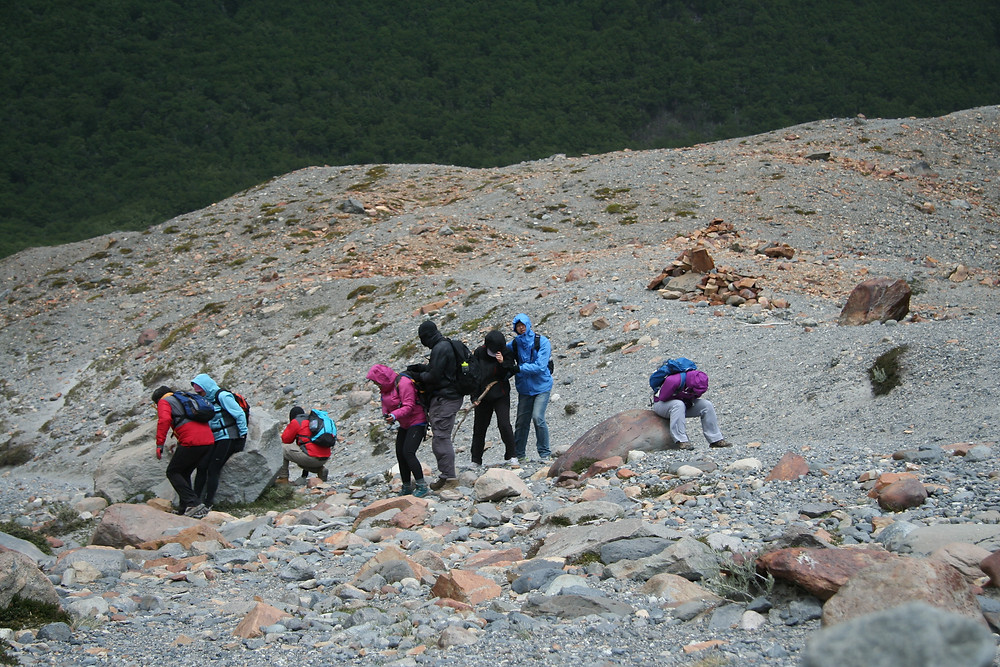 Hikers are trying to protect themselves from the severe wind gusts as they reach Laguna Torre