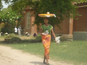 Woman dressed in longyi with thanaka on face carrying belongings