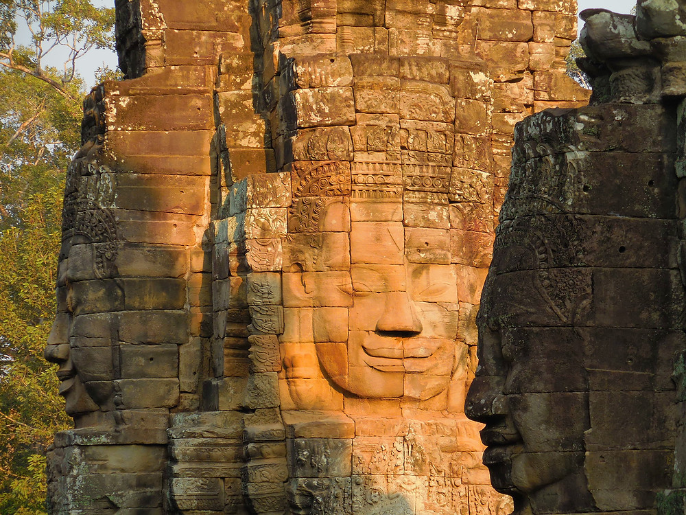 The stone faces of Bayon in different shades of lighting