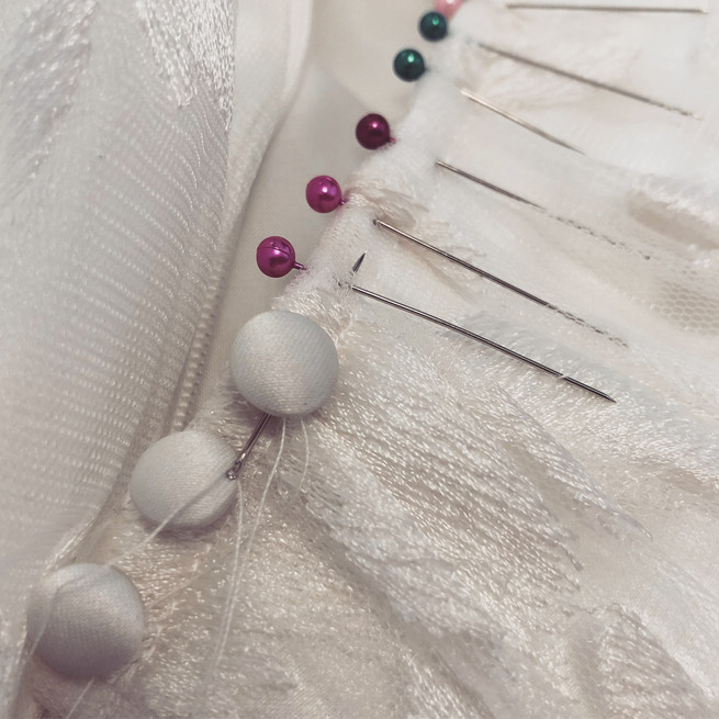 Hand sewing buttons down the back of a bodice