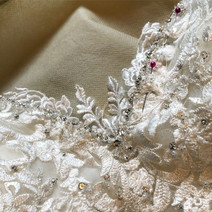 Filling in a revealing bust line with lace motifs, hand stitched and beaded to blend in completely