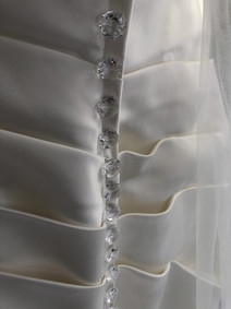 Crystal buttons added to create a back feature on a plain satin dress