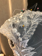 Hand sewing lace motifs to a shoulder