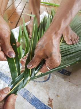 Platting chicken in coconut leaves to be cooked on hot stones!