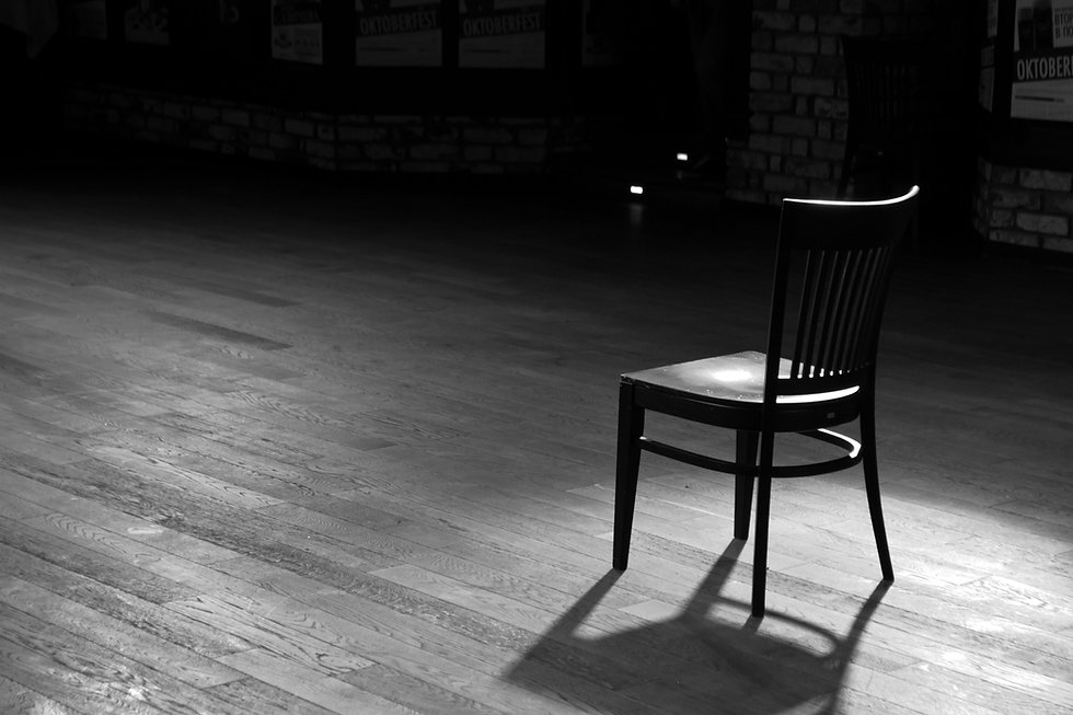 A wooden chair standing in the middle of a stage