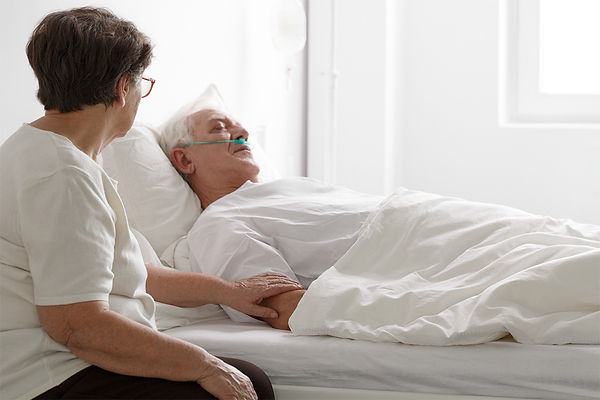 woman sitting with man in hospital, why estate planning is important, covid-19 and estate planning, will, living trust, how to update estate plan, how to create estate plan, updating estate plan, creating estate plan, creating will, updating will