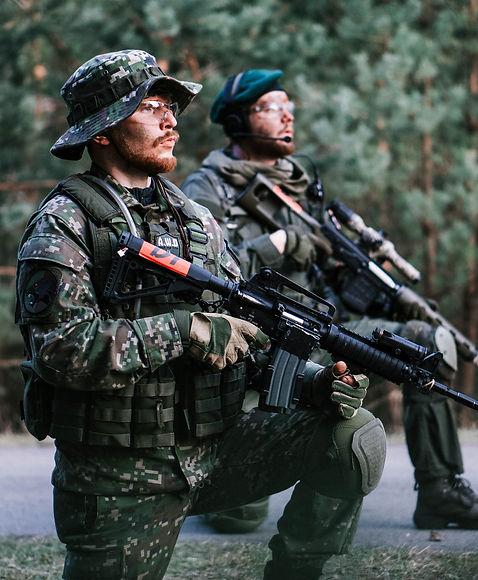 2-men-in-green-camouflage-uniform-holdin