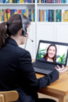 Head of the human resources department with headset in her office in front of her computer, carrying