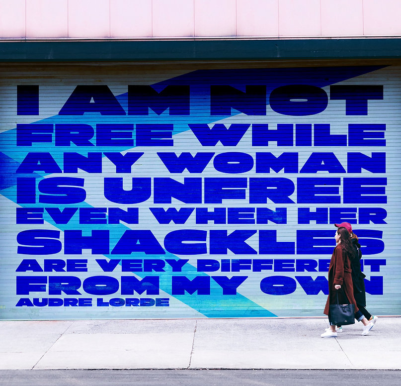 """Two women walk by a mural on large industrial garage door that says in block letters: """"I am not free while any woman is unfree even when her shackles are very different from my own - Audre Lorde. The text is dark blue on a light blue background with teal blue stripes"""