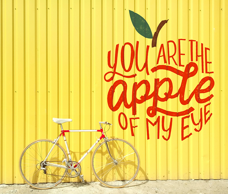 """A mural on a yellow corrugated metal wall with a white and red bicycle in front of it. The mural is in red lettering in the shape of an apple and says """"You are the apple of my eye"""""""