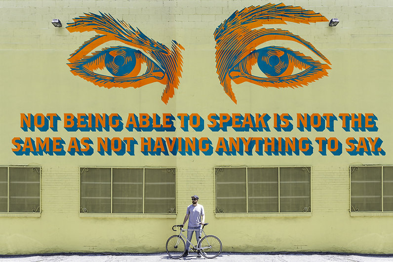 "Large blue eyes with orange shadows look out overtop of text of the same colors that says ""Not being able to speak is not the same as not having anything to say"" Its on a large brick/cement wall with a man holding a bike on a sidewalk."