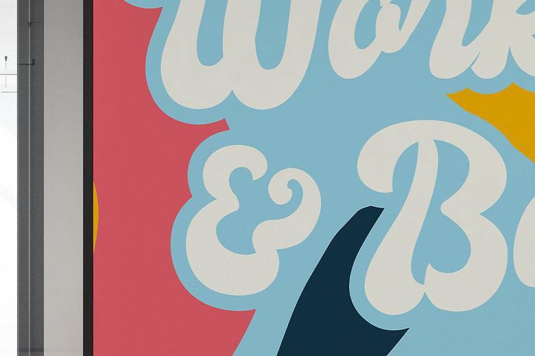 Closeup of seventies white lettering that says Worl Hard & Be Nice, with background of light blue, yellow, coral, and navy blue. Set in an office building