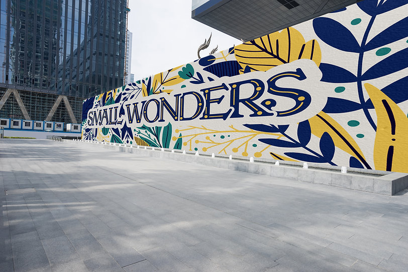 """""""Small Wonders"""" is written in serif text on a large exterior wall, with simple floral designs in navy blue, yellow, and green"""