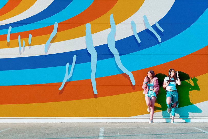 Mural on a cement wall of the outline of the eleven finger lakes in light blue. They all have a drop shadow and the background is wavy stripes in teal, orange, light orange and white. Two women stand with their feet against the wall listening to music.