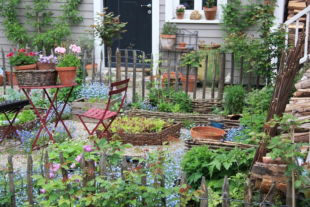 Bauerngarten vor Haus mit in Weidezaun eingefassten Beeten