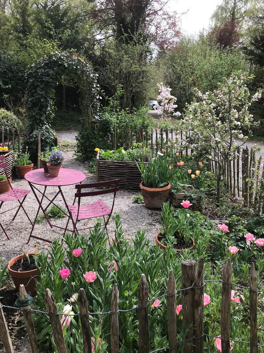 Frühling im Bauerngarten mit blühenden Tulpen und Zierapfel. Roter Tisch in der Mitte