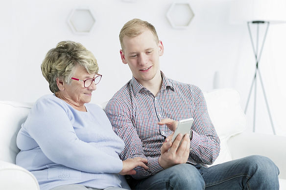 Elderly mother with dementia and son viewing TextCare home monitoring online portal on a mobile phone