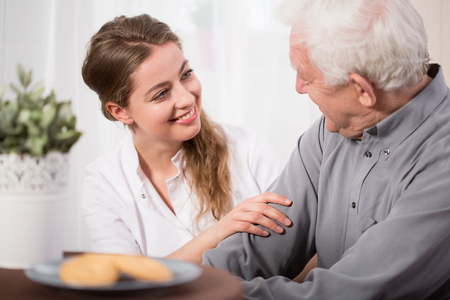 Elderly man being receiving homecare from a friendly carer