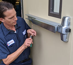Commercial locksmith working on electronic push bar lock in Los Angeles
