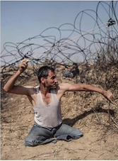 Image of a man throwing a stone over a barbed wire fence. The man has no legs and is sitting on the ground. He is wearing a white tank top and jean shorts.