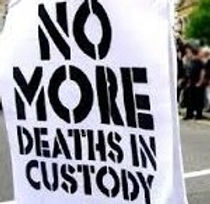 "a sign that reads ""No more deaths in Custody"""