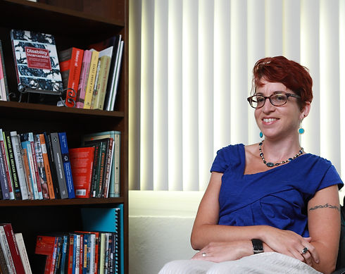 """Image of Liat Ben Moshe sitting next to a bookshelf filled with books. Liat is sitting to the right of the image. She is a white presenting woman with short red hair and glasses. She is wearing a royal blue shirt. The bookshelf to the left of her is showcasing one of her books, """"Disability Incarcerated."""""""